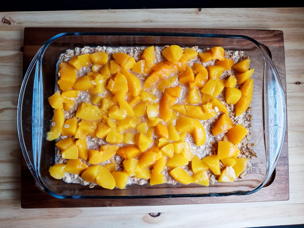 19x13 pan of uncooked baked oatmeal with chopped peached on top.