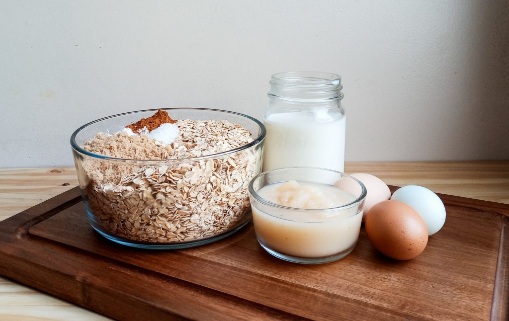 Glass bowl of dry oatmeal and spices, a pint jar of milk, a small bowl of apple sauce and 3 eggs