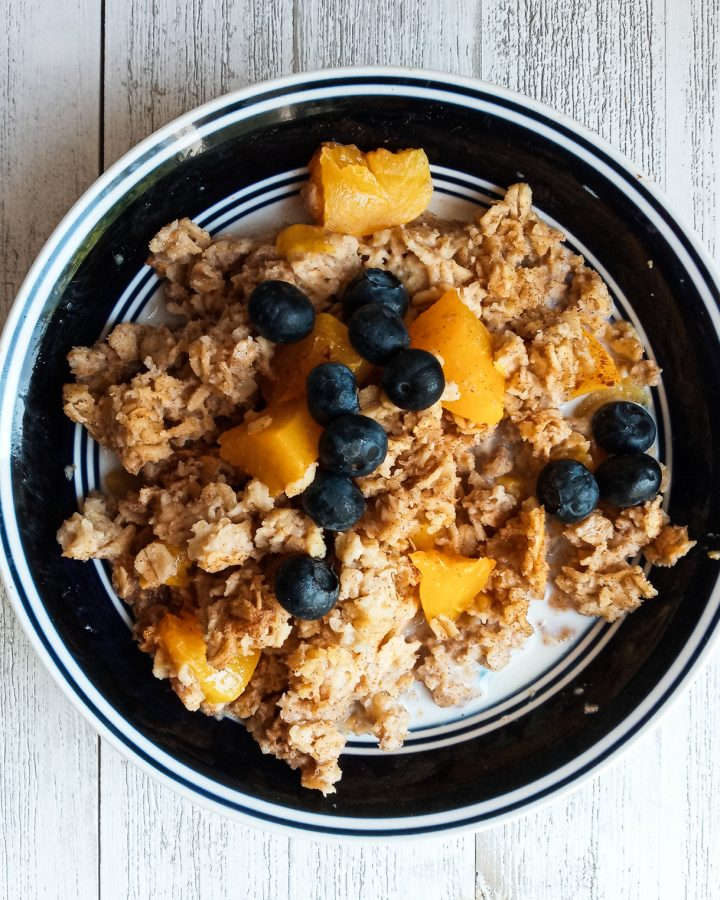 Bowl of baked oatmeal with peaches, blueberries and milk