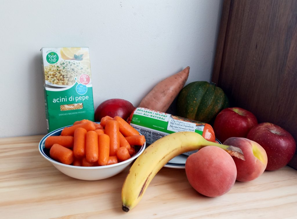 Dry pasta, carrots, banana, peaches, apples, acorn squash, yam and ground turkey sitting on a table,