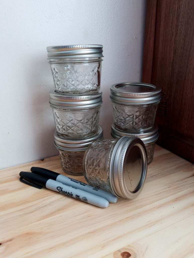 6 glass jelly jars with lids on and 2 permanent markers
