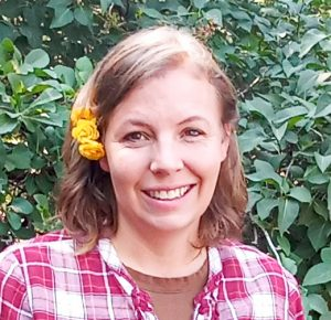 Smiling woman in red plaid shirt with yellow flowers in her hair