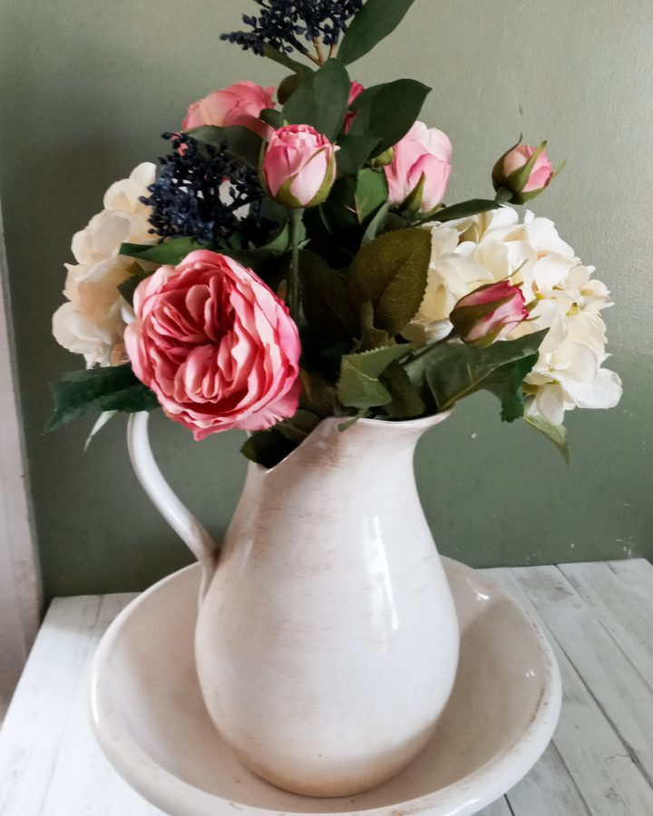 White picture and basin with pink roses, white hydrangeas and blue berries in it