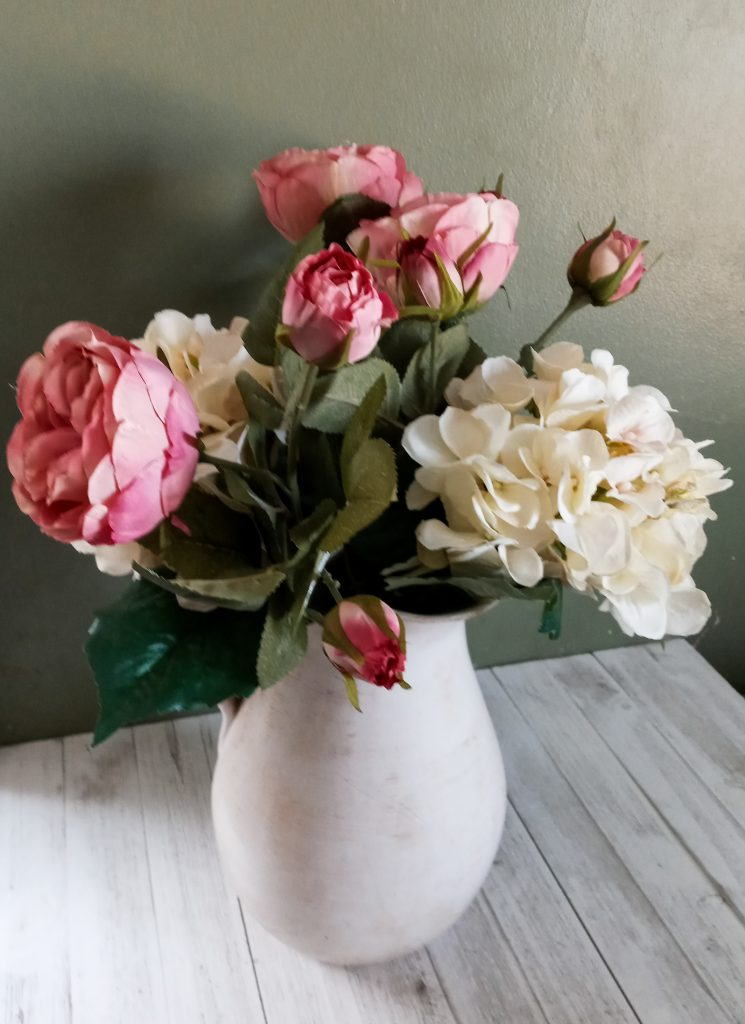 pink and white flowers in a white pitcher