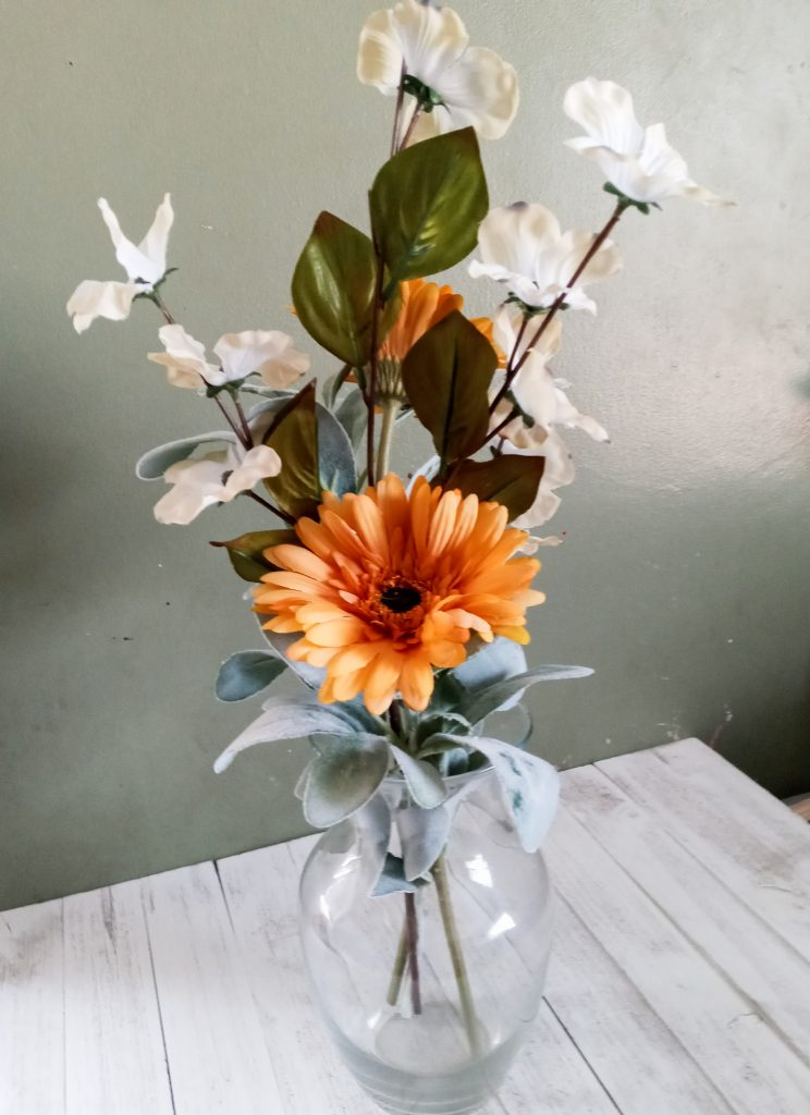 white and yellow-orange flowers in a clear vase