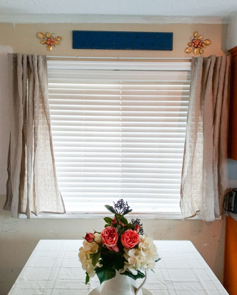 table with a vace of flowers sitting in front of a window